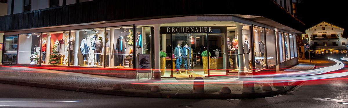 Blick auf die bei Nacht erleuchteten Schaufenster des Modehauses Rechenauer in Oberaudorf